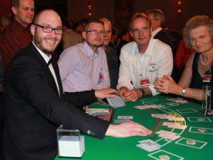 Gute gelaunter Croupier mit Gästen am Blackjack Tisch