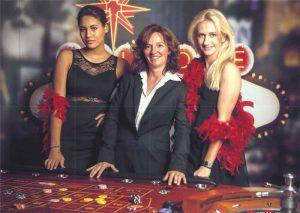 Freundliche Candygirls mit lächelndem Croupier am Roulettetisch