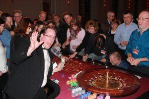Witziger Croupier unterhält die Gäste am Casino Tisch.